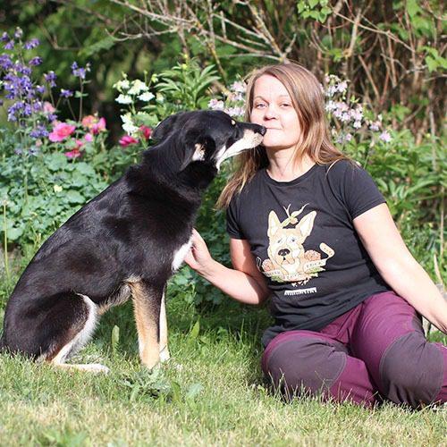 Laura Uotila istuu rescue-koiransa kanssa nurmikolla.