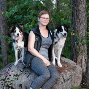 Janita Riikonen istuu metsässä kivellä kahden koiransa kanssa.