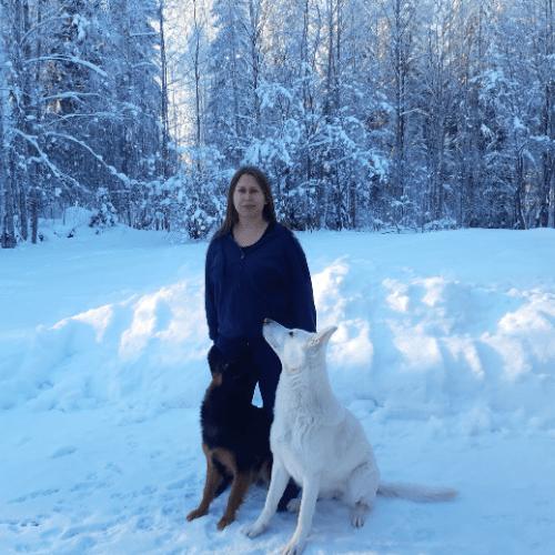 Eläinkouluttaja Minna Simonsson poseeraa kahden koiransa kanssa lumisessa maisemassa.