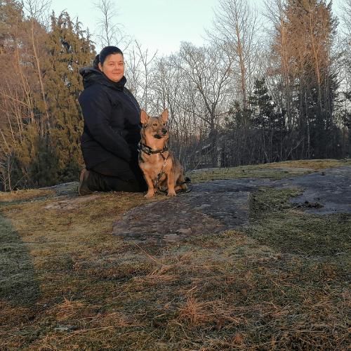 Eläinkouluttaja Nanna istuu kalliolla koiransa kanssa.